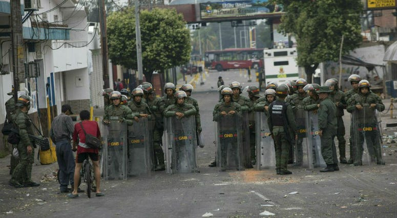 Bolivarian National Guards stand in the street in Urena, Venezuela, as part of Venezuela's closure of the border bridge to Colombia, Sunday, Feb. 24, 2019.