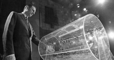 This Feb. 2, 1972, file photo shows Draft Director Curtis W. Tarr spinning one of the two Plexiglas drums in Washington as the fourth annual Selective Service lottery begins.