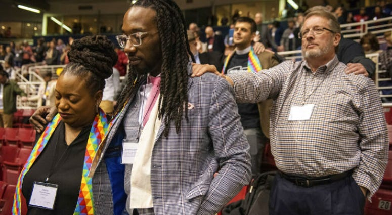 Adama Brown-Hathasway, left, The Rev. Dr. Jay Williams, both from Boston, and Ric Holladay of Kentucky join in prayer during the 2019 Special Session of the General Conference of The United Methodist Church in St. Louis, Mo., Tuesday, Feb. 26, 2019.