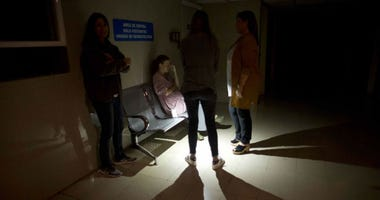 Mothers and relatives wait outside of an intense care room for babies at a clinic, during a power outage in Caracas, Venezuela, Thursday, March 7, 2019.