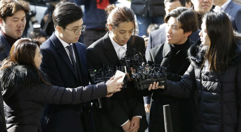 K-pop singer Jung Joon-young, center, arrives at the Seoul Metropolitan Police Agency in Seoul, South Korea, Thursday, March 14, 2019.