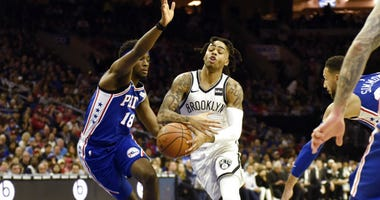 Brooklyn Nets' D'Angelo Russell, center right, drives to the basket as Philadelphia 76ers' Shake Milton defends during the first half of an NBA basketball game.