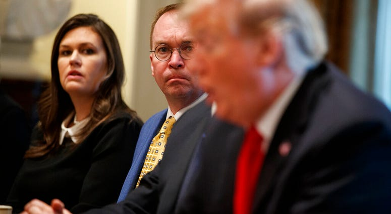 White House press secretary Sarah Sanders and acting White House Chief of Staff Mick Mulvaney listen as President Donald Trump speaks during a meeting with NATO Secretary General Jens Stoltenberg in the Cabinet Room of the White House.