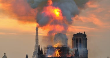 In this image made available on Tuesday April 16, 2019 flames and smoke rise from the blaze at Notre Dame cathedral in Paris, Monday, April 15, 2019.