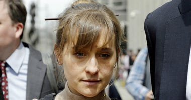 FILE- In this April 8, 2019 file photo, actress Allison Mack leaves Brooklyn federal court in New York after pleading guilty to racketeering charges in a case involving a cult-like group based in upstate New York called NXIVM.