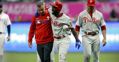 Philadelphia Phillies' Andrew McCutchen, center, is helped by a trainer after being injured while trying to get back to first base during the first inning of a baseball game against the San Diego Padres Monday, June 3, 2019, in San Diego.