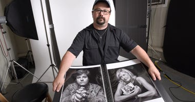 In this June 21, 2019, photo, Paul Gillespie, a photojournalist at the Capital Gazette newspaper, where five people were killed in a mass shooting in June 2018, holds a book of portraits he photographed of survivors and family members of those killed.