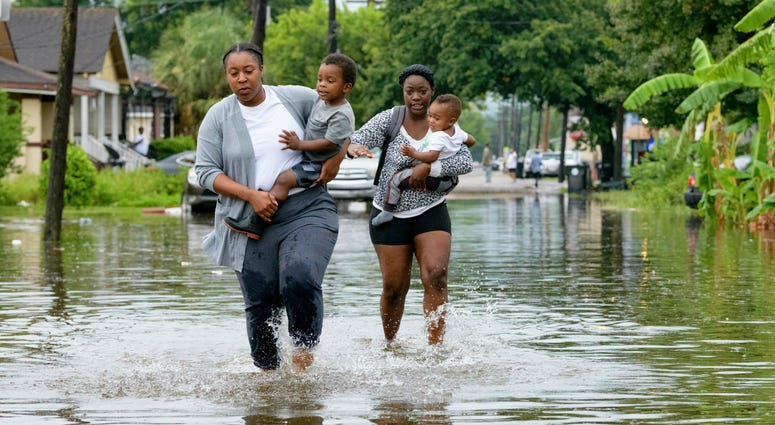 Jalana Furlough carries her son Drew Furlough as Terrian Jones carries Chance Furlough on Belfast Street near Eagle Street in New Orleans after flooding from a tropical wave system in the Gulf Mexico that dumped lots of rain in Wednesday, July 10, 2019.