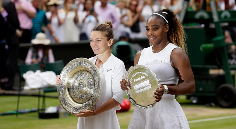 Winner Romania's Simona Halep and second placed United States' Serena Williams, right, pose with their trophies after the women's singles final match on day twelve of the Wimbledon Tennis Championships in London, Saturday, July 13, 2019.