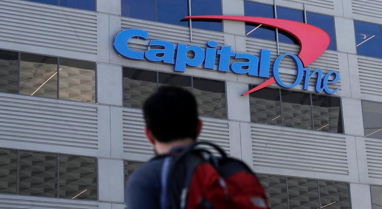 In this July 16, 2019, photo, a man walks across the street from a Capital One location in San Francisco.