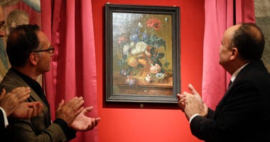 "German Foreign Minister Heiko Mass, left, and Italian Culture Minister Alberto Bonisoli watch the unveiling of the ""Vase of Flowers"" painting by Jan van Huysum, at the Pitti Palace, part of the Uffizi Galleries, in Florence, Italy, Friday, July 19, 2019."