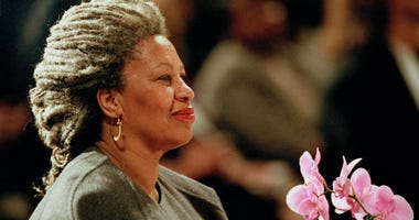 In this April 5, 1994 file photo, Toni Morrison as she holds an orchid at the Cathedral of St. John the Divine in New York.