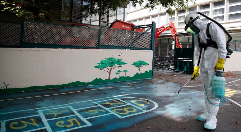 A worker sprays an adhesive product on the ground to gather up the lead particles in the school yard of Saint Benoit primary school in Paris, France, Thursday, Aug. 8, 2019.