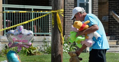 Paul Laughlin, 57, places stuffed animals on Sunday, Aug. 11, 2019 outside a home at 1248 West 11th St. in Erie, Pa., where multiple people died in an early-morning fire.