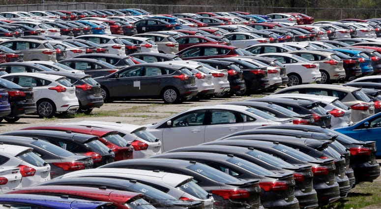 In this May 1, 2015, file photo Ford Focus vehicles are seen on a storage lot in Ypsilanti, Mich. Ford is extending the warranties on about 560,000 small cars to cover a litany of problems with a troubled six-speed automatic transmission.
