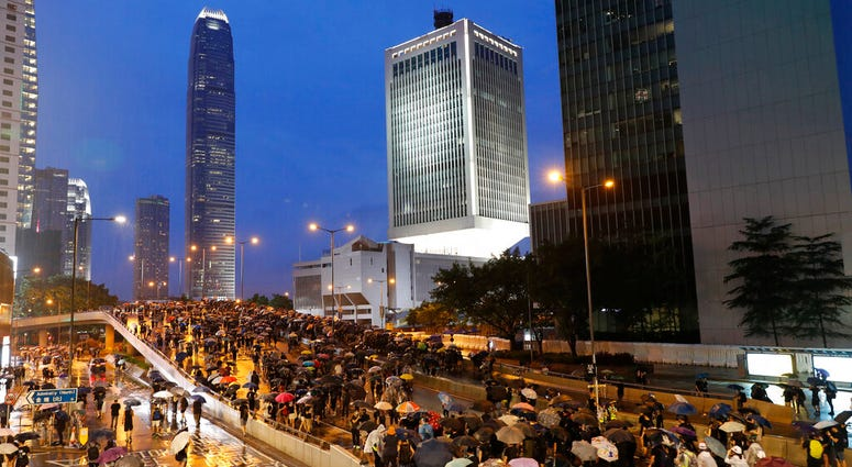 Heavy rain fell on tens of thousands of umbrella-toting protesters Sunday as they marched from a packed park and filled a major road in Hong Kong.
