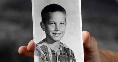 Greg Hunt holds a school photo of himself.