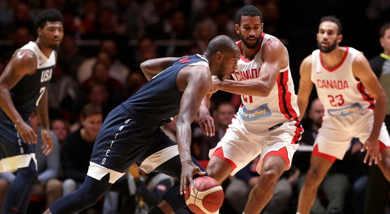 United States' Khris Middleton, second left, goes around the Canadian defenseduring their exhibition basketball game in Sydney, Australia, Monday, Aug. 26, 2019.