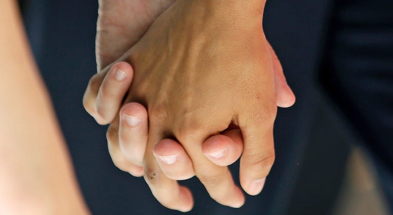 In this Wednesday, July 15, 2015 file photo, a lesbian couple holds hands in Salt Lake City.
