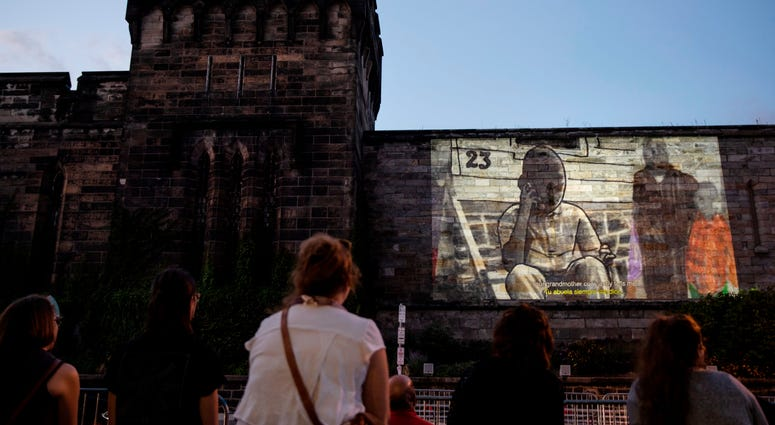 "People view incarcerated filmmaker Robert's animated short titled ""A Special Person"" projected on the wall of Eastern State Penitentiary in Philadelphia."