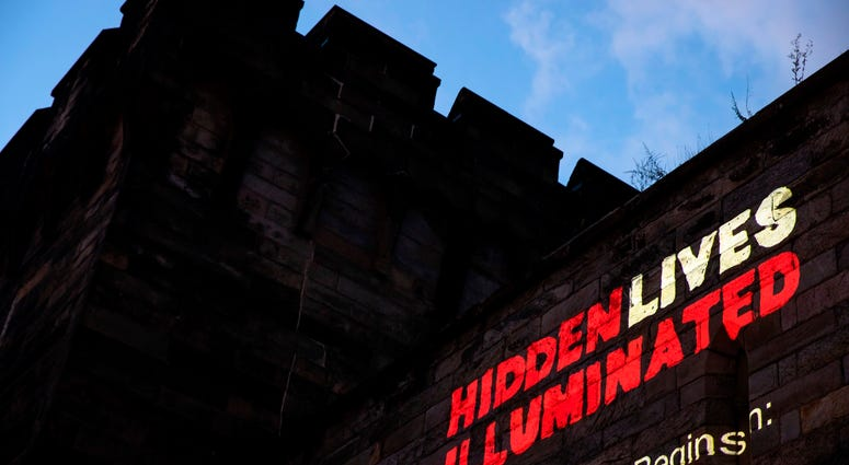 "A new exhibit titled ""Hidden Lives Illuminated"" is projected on a wall of the Eastern State Penitentiary, a former prison that's now a museum."