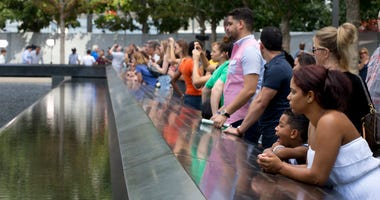 Visitors look at the waterfalls at the World Trade Center Memorial in New York.