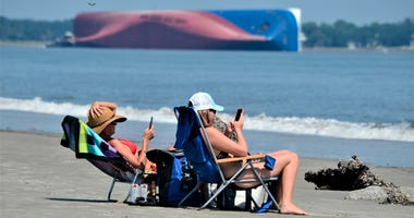 Rachel, left, and Sarah Mitchell look at their phones as they sun bathe on Jekyll Island's Driftwood Beach as the Golden Ray cargo ship is capsized in the background, off the Georgia coast, Sunday, Sept. 8, 2019.