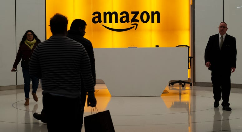 In this Feb. 14, 2019, file photo people walk into the lobby for Amazon offices in New York.