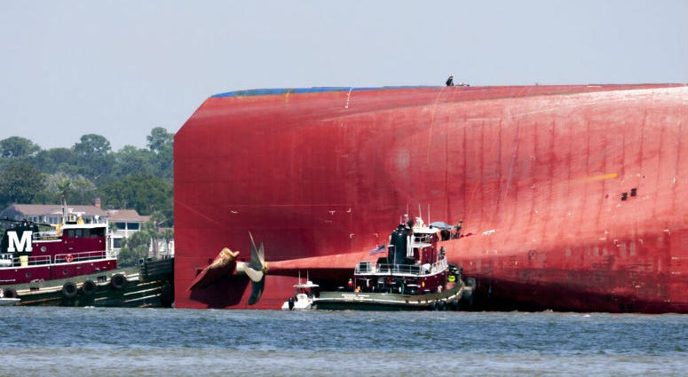 Rescuers work near the stern of the vessel Golden Ray as it lays on its side near the Moran tug boat Dorothy Moran.