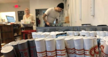 Employees at the marijuana retailer Bridge City Collective in Portland, Ore., can be seen setting up the store for the day behind a row of marijuana products for sale there.