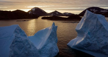 File photo shows an aerial view of large icebergs floating as the sun rises near Kulusuk, Greenland.
