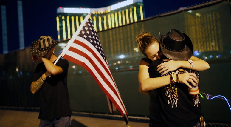 Megan Murphy, right in hat, embraces Cara Knoedler as Kenneth Wright wipes his eyes on the first anniversary of the mass shooting in Las Vegas.