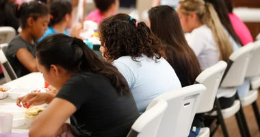 Girls eat lunch at a shelter for migrant teenage girls, in Lake Worth, Fla.