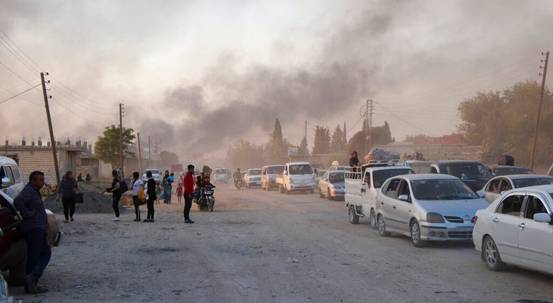 Syrians flee shelling by Turkish forces in Ras al Ayn, northeast Syria.