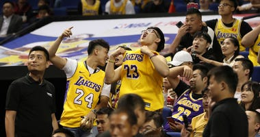 Chinese fans react during a preseason NBA basketball game between the Brooklyn Nets and Los Angeles Lakers at the Mercedes Benz Arena in Shanghai, China, Thursday, Oct. 10, 2019.