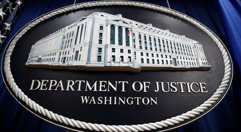 In this Thursday, April 18, 2019, file photo, a sign for the Department of Justice hangs in the press briefing room at the Justice Department, in Washington.
