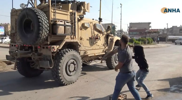 residents who are angry over the U.S. withdrawal from Syria hurl potatoes at American military vehicles in the town of Qamishli, northern Syria, Monday, Oct. 21, 2019.