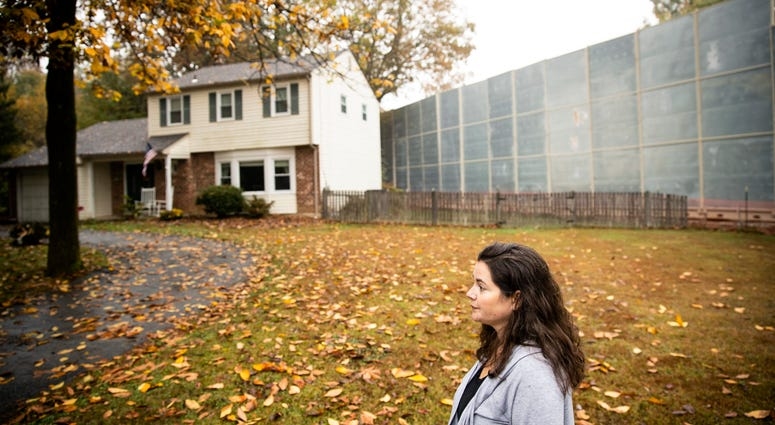 Carrie Gross walks past a construction barrier shielding the Mariner East pipeline near a home during an interview with The Associated Press in Exton, Pa.
