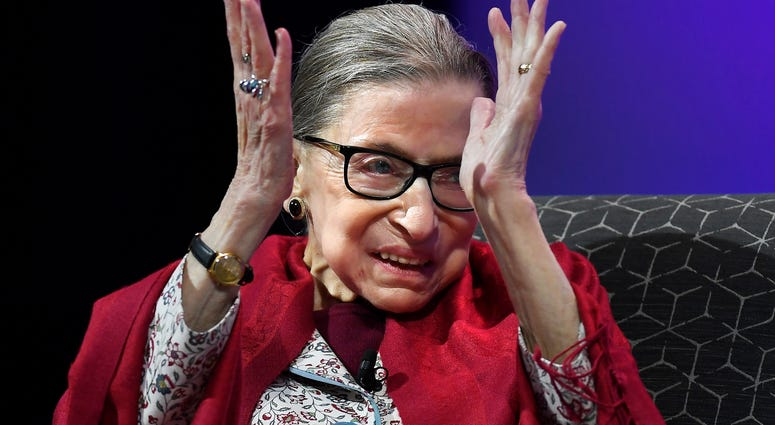 U.S. Supreme Court Justice Ruth Bader Ginsburg claps after listening to students sing opera at Amherst College in Amherst, Mass.