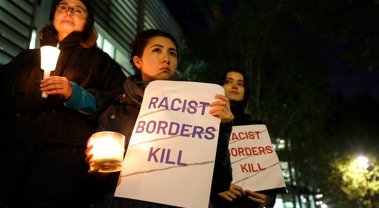 Demonstrators hold banners and candles during a vigil for the 39 lorry victims, outside the Home Office in London.