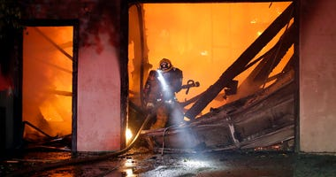 A firefighter works the scene of a wildfire-ravaged home Thursday, Oct. 24, 2019, in Santa Clarita, California.