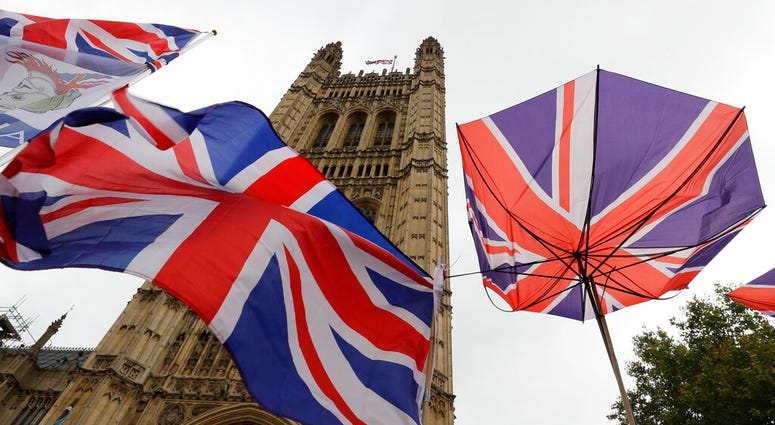 Union flags and an umbrella tied to railings in front of Parliament in London, Friday, Oct. 25, 2019.