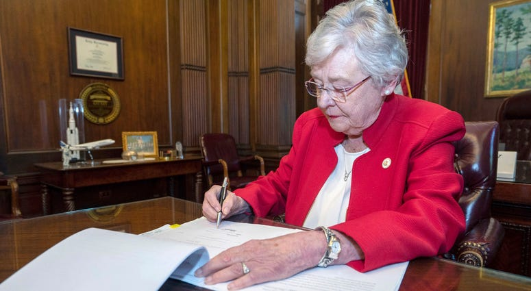 Alabama Gov. Kay Ivey signs a bill that virtually outlaws abortion in the state, in Montgomery, Ala.