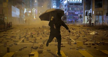 A protester with an umbrella runs away from tear gas fired by riot police on a street scattered with bricks during a protests in Hong Kong, Monday, Nov. 11, 2019.