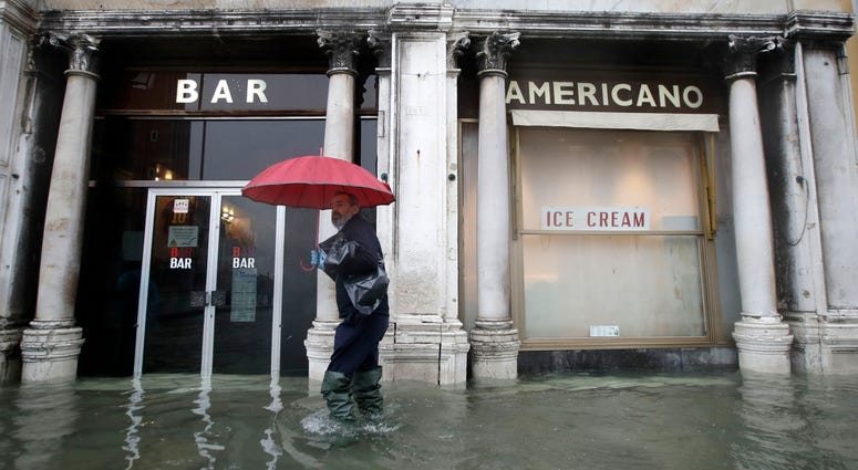 A man walks past a closed cafe in a flooded Venice, Italy, Tuesday, Nov. 12, 2019.