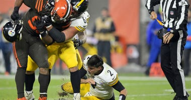 Cleveland Browns defensive end Myles Garrett (95) takes Pittsburgh Steelers quarterback Mason Rudolph's (2) helmet off.