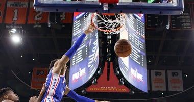 Philadelphia 76ers' Matisse Thybulle, center, dunks the ball with New York Knicks' Dennis Smith Jr., left, defending during the first half of an NBA basketball game, Wednesday, Nov. 20, 2019, in Philadelphia.