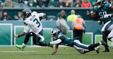 Seattle Seahawks' Russell Wilson, left, tries to avoid Philadelphia Eagles' Rodney McLeod during the first half of an NFL football game, Sunday, Nov. 24, 2019, in Philadelphia.