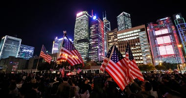 Protesters hold U.S. flags during a demonstration in Hong Kong, Thursday, Nov. 28, 2019.