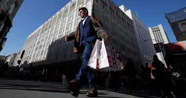 A man carries shopping bags across the street from a Macy's store in San Francisco, Friday, Nov. 29, 2019. Black Friday once again kicked off the start of the holiday shopping season.